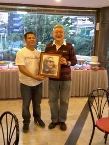 """มงคล วุฒิชัย อดีตนักเคลื่อนไหวก้าวหน้าในแอล.เอ. มอบรูปตัวเองให้เป็นที่ระลึกกับลูกชาย ประธาน บริษัท เอาไว้แขวนที่ร้าน""""บ้านขุนหลวง"""" เชิงสะพานซังฮี้ กทมฯ ในฐานะผู้ก่อตั้ง"""